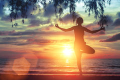 Junges Yogamädchen, das auf dem Ozeanstrand bei erstaunlichem schönem Sonnenuntergang übt nave Stockfotografie