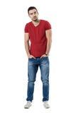 Junges zufälliges Mode-Modell mit den Händen in den Taschen, die weg schauen Stockbilder