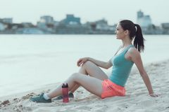 Jungesportfrau steht still, nachdem sie auf Strand gelaufen ist Stockbild