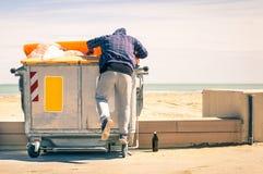 Jungevagabund, der im Abfallbehälter sucht Lebensmittel und nach Re durchstöbert Lizenzfreie Stockfotografie