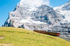 Jungfrau Eigergletscher snowy rocky mountain and red train in Switzerland. Jungfrau Eigergletscher snowy rocky mountain and red train at Switzerland royalty free stock photography