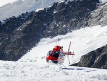 Jungfrau, Switzerlan. Red helicopter on high mountain snow royalty free stock photos