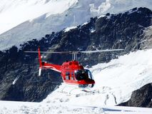 Jungfrau, Switzerlan. Red helicopter on high mountain snow stock photos