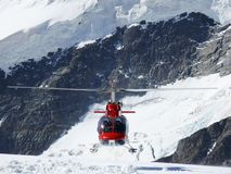 Jungfrau, Switzerlan. Red helicopter on high mountain snow royalty free stock image