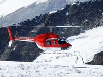 Jungfrau, Switzerlan. Red helicopter on high mountain snow royalty free stock photo