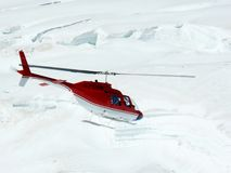 Jungfrau, Switzerlan.  Red helicopter on high mountain snow stock images