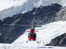 Jungfrau, Switzerlan Rode helikopter op hoge bergsneeuw royalty-vrije stock afbeelding