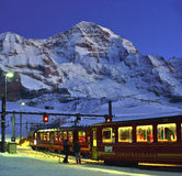 Jungfraubahn and Jungfrau mountain. Red electric train on klaine scheidegg station with junfraujoch mountain in background. Switzerland Royalty Free Stock Photos