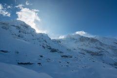 Jungfraujoch, часть швейцарского ландшафта горы снега Альп высокогорного Jungfrau в Швейцарии на солнечном свете с облаками - Вер стоковое фото