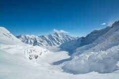 Jungfraujoch, часть швейцарского ландшафта горы снега Альп высокогорного Jungfrau в Швейцарии на солнечном свете с облаками голуб стоковое фото