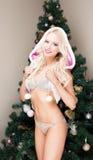 Jungfru- sexig ung kvinna för härlig blond snö i en rosa dräkt och huv på julgranen Nytt år jul, x-mas som är ny Arkivbild
