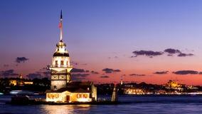 Jungfru- torn eller Kiz Kulesi med att sväva turist- fartyg på Bosphorus i Istanbul på natten Arkivfoto