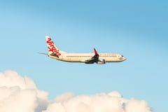 Jungfruliga flygbolag som flyger i molnen Arkivfoton