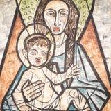 Jungfruliga Mary med behandla som ett barn Jesus som målas på en vägg av den forntida cemen Arkivbild