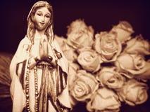 Jungfruliga Mary moder av statyetten för statyett för staty för radband för gud den be kristna och vita rosor Royaltyfri Fotografi