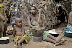 Jungle of CAR. Africa. Jungle of the Central-African Republic. Baka woman cooks food, crushing a flour in a mortar Stock Photo