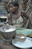 Jungle of CAR. Africa. Jungle of the Central-African Republic. Baka woman cooks food, crushing a flour in a mortar Stock Photography