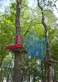 Jungle gym. Wooden platforms and blue net hanged between the trees stock photo