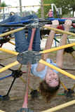 Jungle Gym Girl 2. A young girl hanging upside down from a jungle gym in the park stock photography