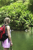 Jungle Hiking. A woman surveys a pool of water in a lush jungle setting. The hiker is ready to take a dip in the water Stock Photo