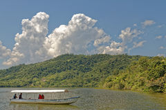 Jungle lake boat with tourists Royalty Free Stock Photos