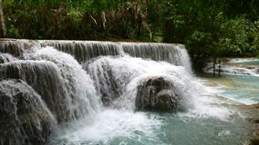 Jungle landscape with cascading water stream and natural swimming pools. Kuang Si Falls in Laos, around 30 km from Luang Prabang. A Cascading rain forest stream stock footage