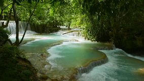 Jungle landscape with cascading water stream and natural swimming pools. Kuang Si Falls in Laos, around 30 km from Luang Prabang. A Cascading rain forest stream stock video footage