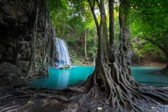 Jungle landscape with Erawan waterfall. Kanchanaburi, Thailand. Jungle landscape with flowing turquoise water of Erawan cascade waterfall at deep tropical rain Royalty Free Stock Photography