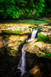 Jungle landscape with flowing turquoise water of georgian cascade waterfall at deep green forest. Mountain of georgia Royalty Free Stock Images