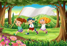 A jungle with three kids with an empty banner Royalty Free Stock Photography