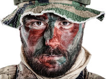 Jungle warfare closeup. Special forces United States in Camouflage Uniforms studio shot. Wearing jungle hat, Shemagh scarf, painted with red and green face Royalty Free Stock Photo