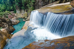 Jungle waterfall with flowing water, large rocks Royalty Free Stock Images