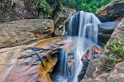 Jungle waterfall with flowing water, large rocks Stock Images