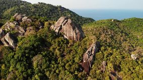 Jungles and mountains of tropical island. Drone view of green jungles and huge boulders on volcanic rocky terrain of Koh. Tao Island on sunny day in Thailand stock footage