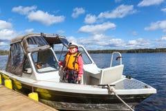 Jungs-Kind in Kappe Kapitäns, die auf hölzernem Pier in festgemachtem Motorboot steht Stockfotos