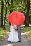 Jungvermählten auf der Straße mit einem roten Regenschirm lizenzfreies stockbild