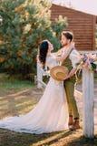Jungvermählten in der Cowboyart, die auf Ranch steht und umarmt stockbild
