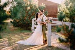 Jungvermählten in der Cowboyart, die auf Ranch steht und umarmt stockfotos