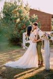 Jungvermählten in der Cowboyart, die auf Ranch steht und umarmt lizenzfreies stockbild