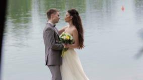 Jungvermählten, die auf dem Hintergrund des Flusses küssen stock video footage