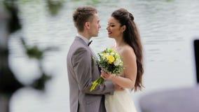 Jungvermählten, die auf dem Hintergrund von Fluss küssen stock footage