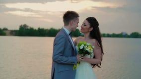 Jungvermählten, die auf dem Hintergrund von Fluss küssen stock video footage