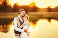 Jungvermählten, die gegen den roten Sonnenunterganghintergrund sich umarmen Lizenzfreie Stockfotografie