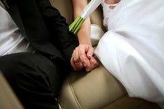 Jungvermählten, die ihre Hände halten Lizenzfreie Stockfotografie