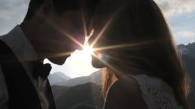 Jungvermählten im Liebeskuß in den Strahlen des Hochs der untergehenden Sonne in den Bergen stock video
