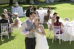 Jungvermählten-Paare, die Champagne In Garden rösten Stockbilder