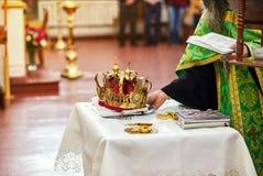 Jungvermähltenaustauscheheringe auf einer Zeremonie in der Kirche lizenzfreie stockfotografie