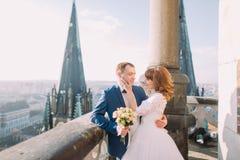 Jungvermähltenbraut und -bräutigam, die auf dem Balkon der alten gotischen Kathedrale mit Stadtansicht am Hintergrund aufwerfen lizenzfreie stockfotos
