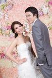 Jungvermähltenbraut und -bräutigam, die mit Blumendekoration im backgr aufwerfen Lizenzfreie Stockfotografie