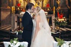 Jungvermähltenbraut und -bräutigam küssen zuerst an der Hochzeitszeremonie im churc Lizenzfreie Stockfotografie